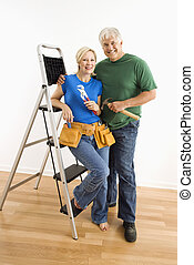 Man and woman with tools and ladder. - Middle-aged couple...