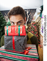 Man Looking Over Stacked Christmas Gifts In Store - Portrait...