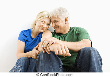 Man and woman snuggling. - Middle-aged couple sitting...