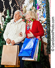 Senior Couple Shopping In Christmas Store - Senior couple...