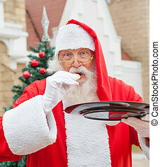 Santa Claus Eating Cookie Against House - Santa Claus eating...