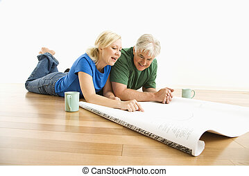 Man and woman discussing blueprints - Middle-aged couple...