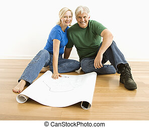 Man and woman with blueprints - Middle-aged couple sitting...