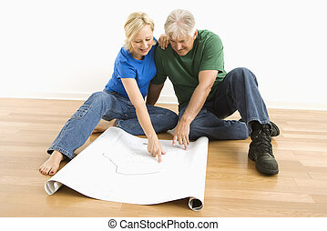 Man and woman looking at blueprints - Middle-aged couple...