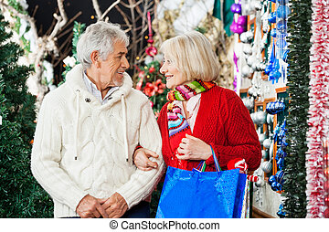 Senior Couple With Shopping Bags At Christmas Store - Senior...