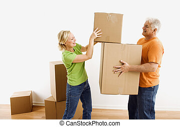 Man and woman moving boxes. - Middle-aged man holding...