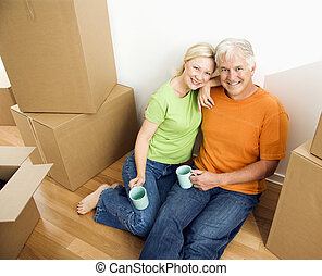 Man and woman with moving boxes - Middle-aged couple sitting...