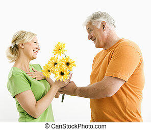 Man giving woman bouquet - Middle-aged man giving woman...