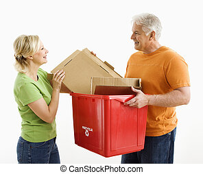 Man and woman recycling - Man holding recycling bin while...