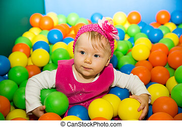 Happy child girl in colored ball on playground. The concept...