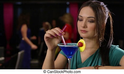 Pensive clubber - Close-up of a pensive young lady drinking...