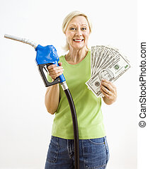 Happy woman with gas pump and money. - Portrait of smiling...