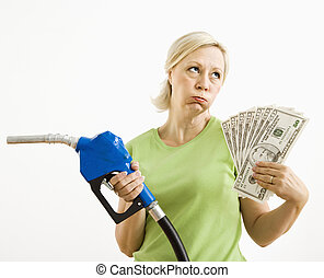 Unhappy woman with gas pump and money.
