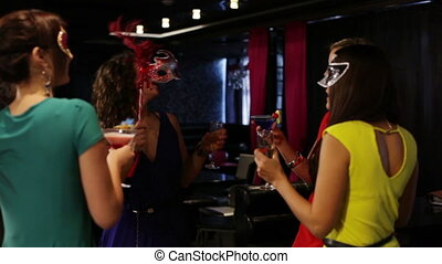 Theme party - Masked ladies with cocktails taking part in a...