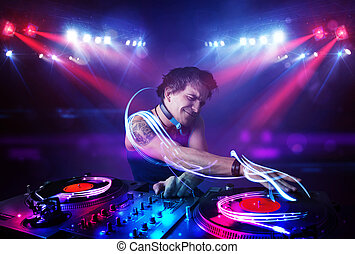 Disc jockey playing music with light beam effects on stage -...