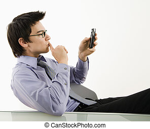 Man looking at cell phone. - Asian businessman sitting at...