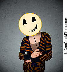 Young woman holding a smiley face emoticon - Young lady...