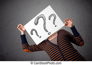 Young woman holding a paper with drawed question marks on it...
