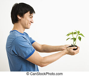 Man holding plant. - Asian man standing holding growing...