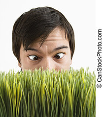Cross-eyed man behind grass. - Asian young man looking over...