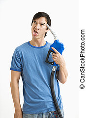 Man holding gas nozzle to head.