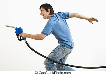Man aiming gas nozzle. - Asian young man aiming gasoline...