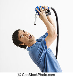 Man with gas nozzle. - Asian young man fighting with...