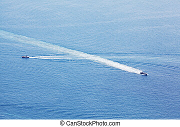 Intersection of two power boats in the ocean with long prop wash lines