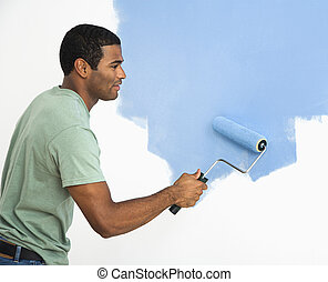 Handsome man painting wall - African American man painting...