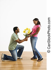 Man giving woman flowers - African American male giving...