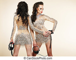 Fete Clubbing Two Women in Shiny Silver Dresses with...