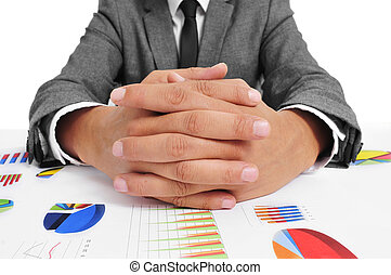 man wearing a suit sitting in a table full of charts with clasped hands