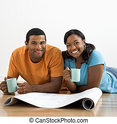 Couple with blueprints - African American male and female...