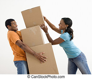 Couple with moving boxes. - African American woman placing...