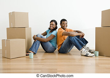 Portrait of couple with boxes. - African American male and...