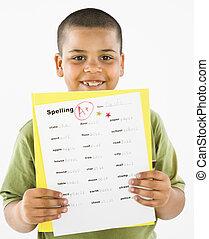 Smiling hispanic boy holding homework. - Young boy proudly...