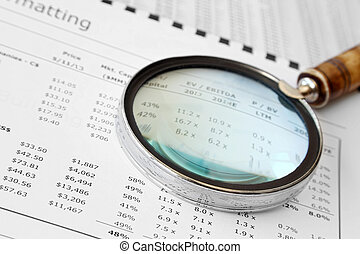 Magnifying Glass Over Financial Doc - Close-up of magnifying...
