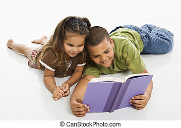 Boy and girl reading book together.