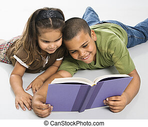 Brother and sister reading book together. - Hispanic brother...