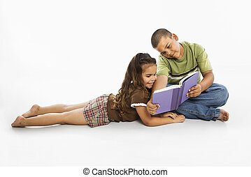 Hispanic boy and girl reading book together.
