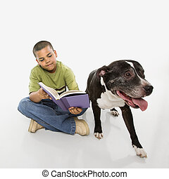 Boy reading book with dog. - Young hispanic boy reading book...