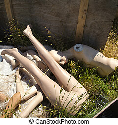 Old mannequin parts on ground. - Leg and torso of old...