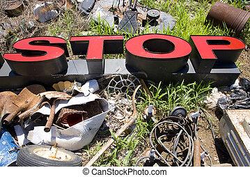 Letters spelling STOP in trashy junkyard - Word STOP lying...