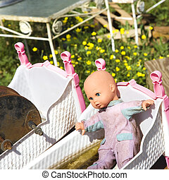Baby doll in crib - Old discarded baby doll lying in crib in...