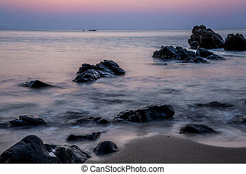 Pink sky over a rocky seashore. Sunset landscape. Thai Boat....