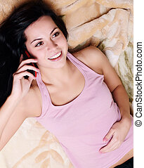 Beautiful happy young woman relaxing on couch and using...
