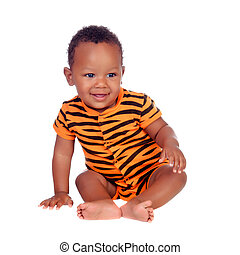 Adorable african baby with with brindle pajamas sitting on...