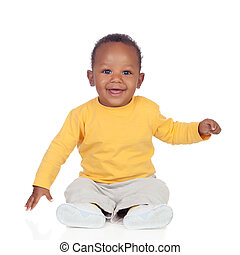 Adorable african baby sitting on the floor isolated on a...