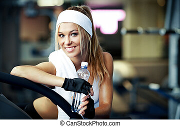 Fitness on a treadmill - Smiling athletic woman resting on a...