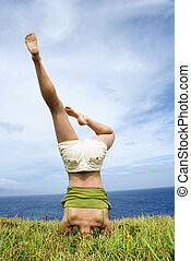 Woman doing headstand - Young woman doing headstand in grass...